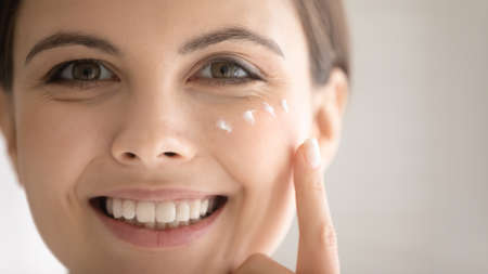 Close up cropped head shot portrait smiling beautiful woman with healthy skin applying moisturizing face cream on cheekbone, attractive happy girl looking at camera, enjoying skincare routine Stock Photo