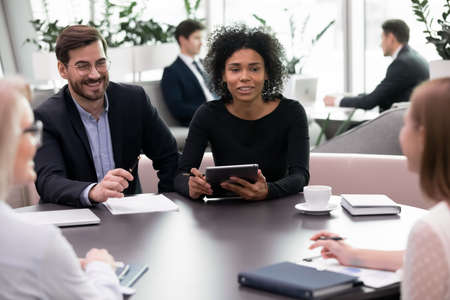 Friendly team of recruiters listen female job position candidate interview. Smiling mix race business people satisfied with employee answers and skills. Good first impression and employment Stockfoto