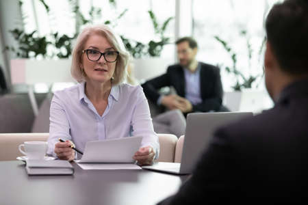 Adult business woman interviewing job candidate. Experienced businesswoman ask questions to male applicant holding his resume. Recruiter and employee meeting. Human resources and hiring concept Stockfoto