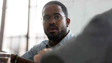 Serious concerned African mixed-race businessman participant listens opponent during group business meeting, solve issues, involved in training, negotiations process between business parties concept