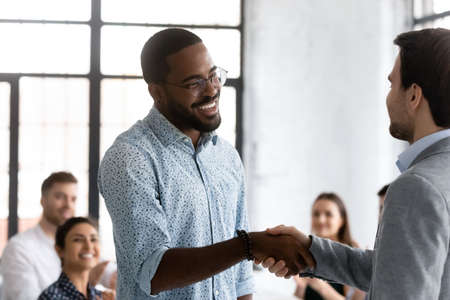 African employee got promotion at work feels happy shake hands with company head at boardroom with diverse staff. Career growth, sales increase, praise and recognition, enjoy moment of success concept