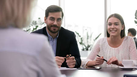 Successful job interview, two headhunters happy smiling listen to employee. Female candidate making good impression on team of hr managers during meeting. Adult business woman getting new position