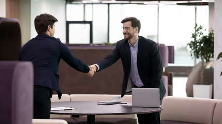 Job interview, business man handshaking with young candidate. Mature recruiter and young professional shaking hands during meeting. Hr manager and employee, financial consultant and client greeting