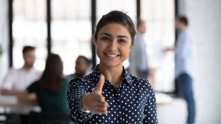 Head shot of friendly indian boss greeting client stretch out hand welcoming express amity good manners meet job vacancy applicant, first acquaintance, human resource HR manager recruiter work concept Stockfoto
