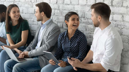 Cheerful diverse applicants hold devices talking while waiting turn job interview. People gather in office prepared for seminar, communicating enjoy chat and friendly relations in collective concept