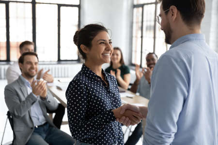 Happy proud excited Indian ethnicity employee get promotion receive praises from boss and cheering and congratulations from diverse staff members shake hands with chief. Recognition of success concept