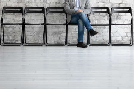 Man sit cross legs on chair in office bank corridor while wait turn with advisor or job interview feels tranquil and confident, has chance loan application approve, got position in company. HR concept Stockfoto