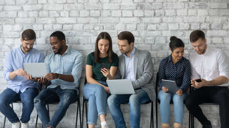 Six multi racial millennial girls and guys sit in line on chairs against grey wall using diverse devices, busy students discuss tasks, employees wait seminar in corridor having fun in internet concept Stockfoto