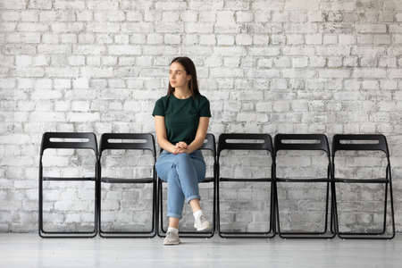 Young woman sit on chair looking away, applicant wait for job interview feels confident. Lost in thoughts, in anticipation of getting opportunity chance receive company vacant place, to prove herself