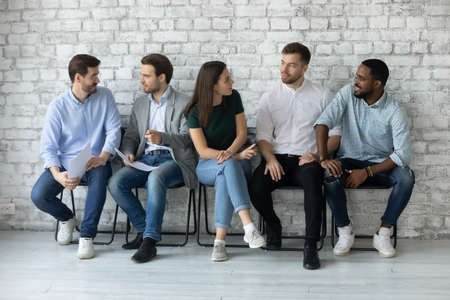 Involved in friendly conversation diverse people one girl multi ethnic guys sit on chairs in office hall wait for group meeting or seminar discuss work moments. Job interview applicants talk concept Stockfoto