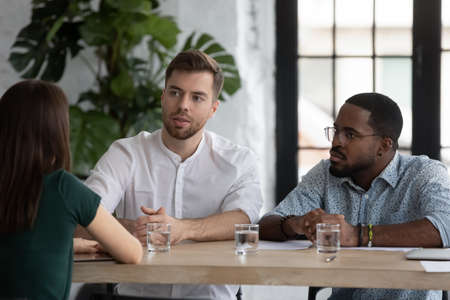 Multi-ethnic group of businesspeople sit at table negotiating during meeting in office board room, client and executives communication. HR manager and unconvincing applicant at job interview concept