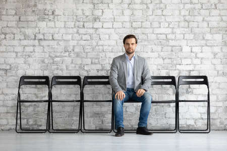 Man in jacket sit on chair alone in office hallway looking at camera feels confident and motivated hope for getting vacant place in company, prepared for job interview. HR, recruiting agency concept