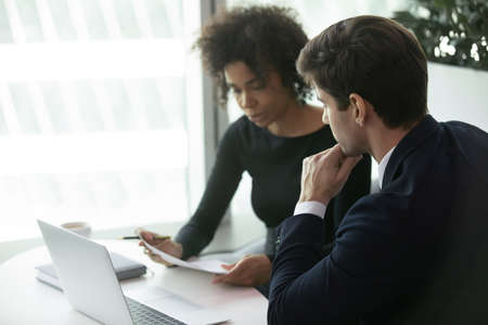 African american business woman reading resume of male employee during job interview. Human resources manager examining candidate cv. Young businessman looking at female boss with business report