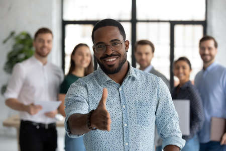 Mixed race sales manager stretch out hand introduces himself to client, greeting shake hands company customer, employees on background. Formal appointment, HR job interview, business etiquette concept