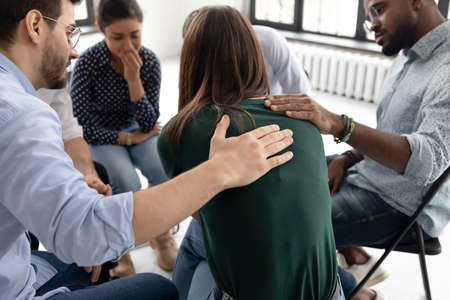 Multi ethnic people gathered together sitting on chairs in circle supporting crying desperate girl during group therapy session, medical detox center, psychological help assistance at meeting concept