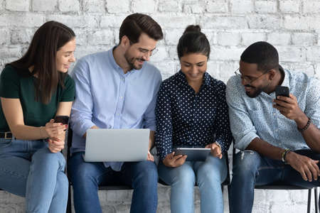 Four multi ethnic millennial girls and guys gather in office hall sit on chairs wait for briefing corporate meeting enjoy free time with gadgets internet fun together, electronic devices users concept