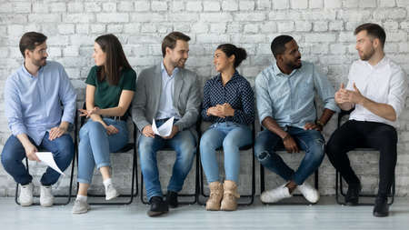 Group of multi ethnic people gathered in office corridor sitting on chairs in line talking with competitors while waiting turn job interview. HR, recruiting agency participants job-seekers concept