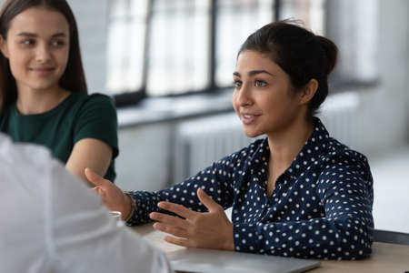 Indian woman applicant is interviewed by HR managers during job interview, answer question feels confident. Business negotiations process, discuss deal contract terms, leadership coaching work concept