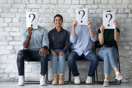 Girl applicant sit on chair with unknown diverse competitors people hiding face behind paper sheets with question mark, successful Indian qualified specialist passed job interview successfully concept