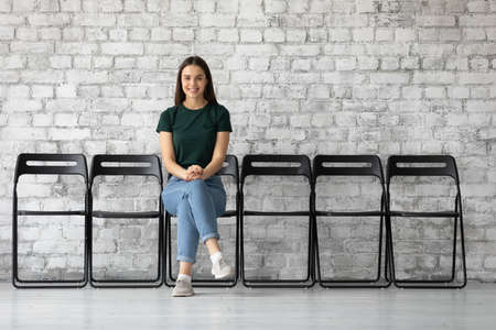 Smiling young woman company vacancy candidature sit on chair feels confident about future job interview, receive opportunity got hired. Human resources, satisfied client of commercial services concept Stockfoto