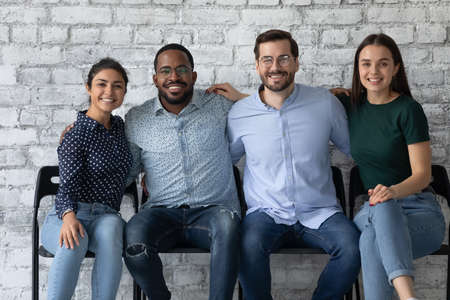 Four multi ethnic students friendly office employees sit together on chairs embracing smiling looking at camera. Warm relations between company members, amity and friendship, racial equality concept Stockfoto