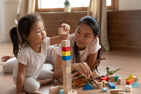 Interested little biracial baby girl in casual wear sitting on warm floor with affectionate smiling loving vietnamese mother or caring babysitter, playing with wooden cubes together in living room.