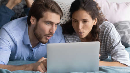 Interested young man and woman looking at laptop screen together, lying in bed at home, puzzled surprised couple reading good news in email, great shopping offer, watching video in social network 写真素材