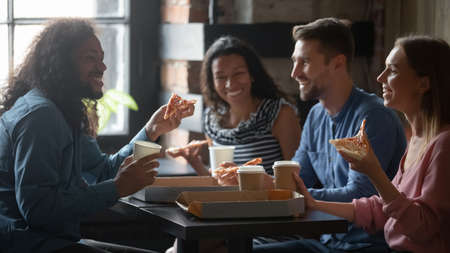 Mixed-race caucasian friends sit at table in cafe eat pizza drink coffee having funny talk. Sharing ordered pizza slices spend Friday in pizzeria yummy fast food. Racial equality, friendship concept