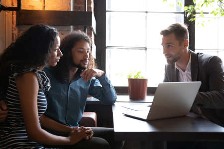 Real estate agent company representative tell to mixed-race couple about new great offer showing new home project online presentation use pc, insurance broker and potential buyers meet in cafe concept