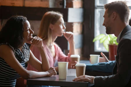 Multi ethnic couples sitting in cafe enjoy chatting, focus on African girl flirting with Caucasian guy during speed dating romantic meeting participation. Love seekers, romantic relationships concept