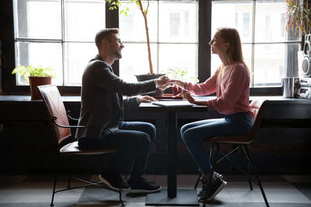 Female HR manager and male applicant shake hands greeting each other start job interview sit in cafe table. Client and services representative accomplish negotiations reached agreement feels satisfied