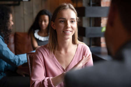 Speed dating, sympathy, flirtation, search partner and love concept. Young woman sitting in cafe participates in matchmaking event activity telling about herself enjoy communication with rear view guy