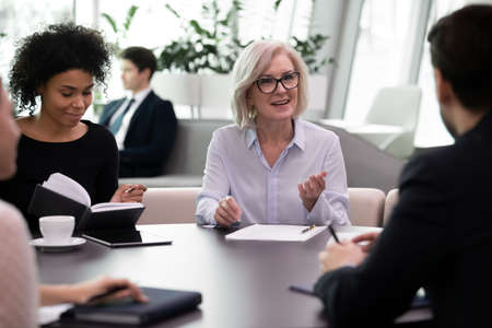 Aged female mentor conducting meeting with young professionals. Mix race business people group listen to experienced leader or coach while training. Young managers consulting with older businesswoman