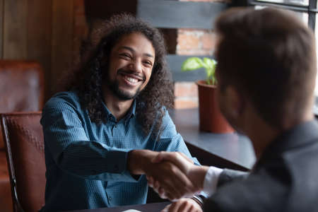 Mixed-race successful applicant express gratitude shake hands with employer got hired at company position accomplish job interview meeting in cafe. African Caucasian businessmen make deal handshaking