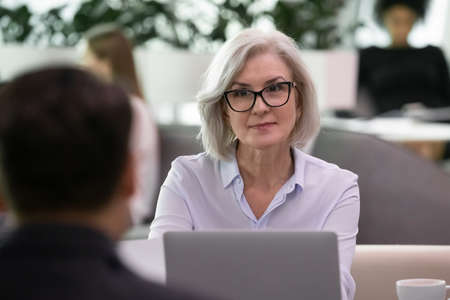 Experienced human resources manager listening vacancy candidate during job interview. Female hr or employer meeting with applicant explaining his resume. Business recruitment and employment concept Foto de archivo