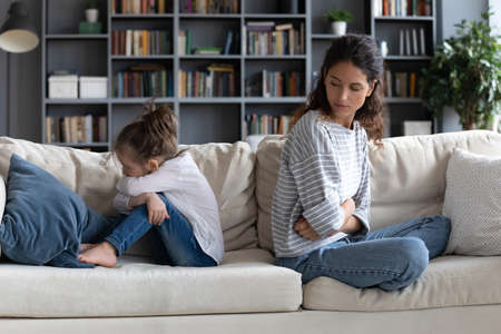Unhappy mother and stubborn little daughter ignoring each other, sitting back to back on couch in living room, offended young mum and upset preschool girl not talking, family conflict concept