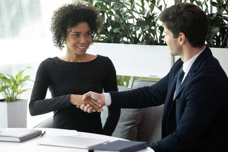 Successful business meeting or job interview with businessman and businesswoman handshaking. Male recruiter and mixed race female applicant handshake. Happy smiling candidate shaking employer hand
