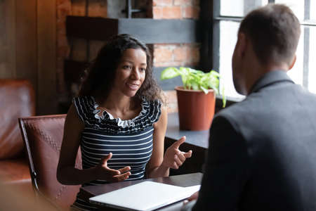 African applicant answer questions at job interview meeting in cafe with employer. Human resources, staffing process. Client and representatives communication, make offer sell company services concept Stockfoto