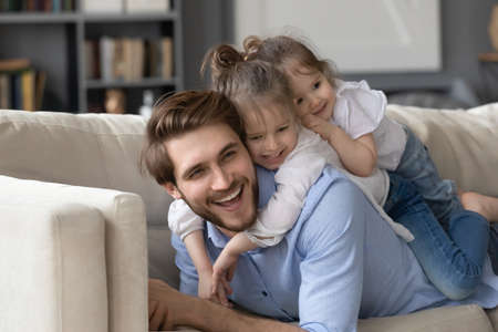 Two cute little girls lying on smiling father back, relaxing on cozy couch together, enjoying leisure time, lazy weekend, happy young dad and affectionate preschool daughters having fun at home