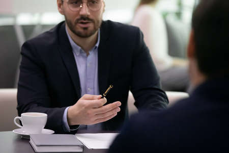 Business man explaining contract or deal destails to employee. Job interview meeting closeup with hr manager describing vacancy and interviewing male candidate. Two male businessmen partners Stockfoto