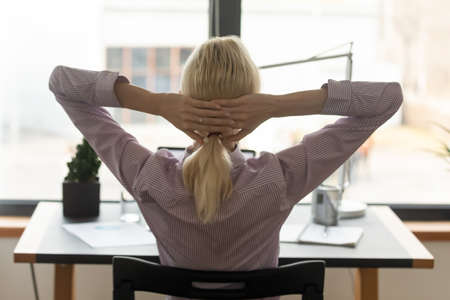 Back view of exhausted blonde woman lean in chair relax at workplace, take nap or daydream, tired female employee rest at table, breathe fresh air, relieve negative emotion, stress free concept 写真素材