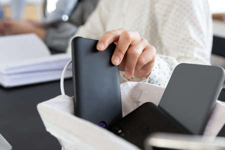 Close up of female employee leaving smartphone engaged in team meeting in office, woman worker place cellphone gadget in basket attending no cell allowed briefing or conference in boardroom