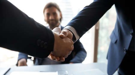 Close up focus on two male hands shaking. Two businessmen in formal wear handshaking, making welcoming gesture at formal meeting or celebrating agreement cooperation establishing partnership.