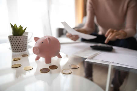 Close up focus on piggy bank with coins on table, woman on background manage family finances, calculate expenses on calculator, female saving money for future investment, pay bills taxes, plan budget