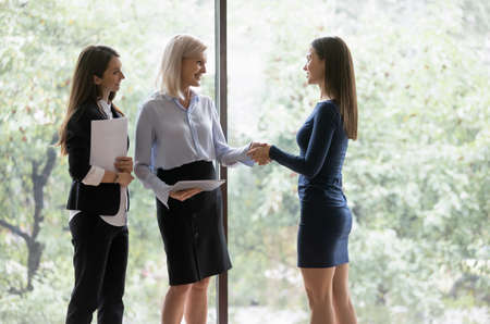 Middle-aged businesswoman greeting millennial female colleague different age business women shake hands express respect smiling, good first impression, hr manager congratulate hired applicant concept
