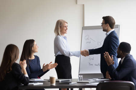 Boss express gratitude to old worker shake hands great work done, best employee of month got reward, promoted, career advance. Client and executive manager greet each other start group meeting concept