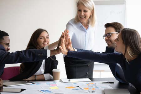 Happy diverse 5 businesspeople giving high five gesture attending at corporate team building activity. Celebration of success and career achievements, unity team spirit, loyalty and support concept