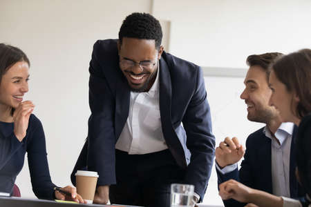 African employee leader laughing during briefing meeting with co-workers in office. Multi ethnic businesspeople gather together have fun rest at break enjoy conversation friendly atmosphere with mates