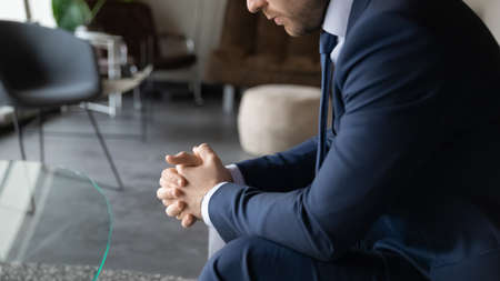 Crop close up of depressed pensive businessman in formal suit lost in thoughts ponder over problem solution, serious male boss director with hands clenched thinking considering company business idea