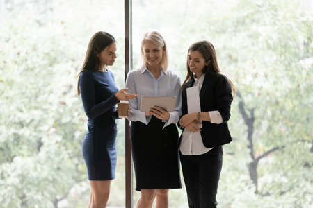 60s and young women colleagues standing in office hall use tablet device resting during break discuss e-commerce purchase sales and discount special offer, virtual shopping website enjoy informal talk